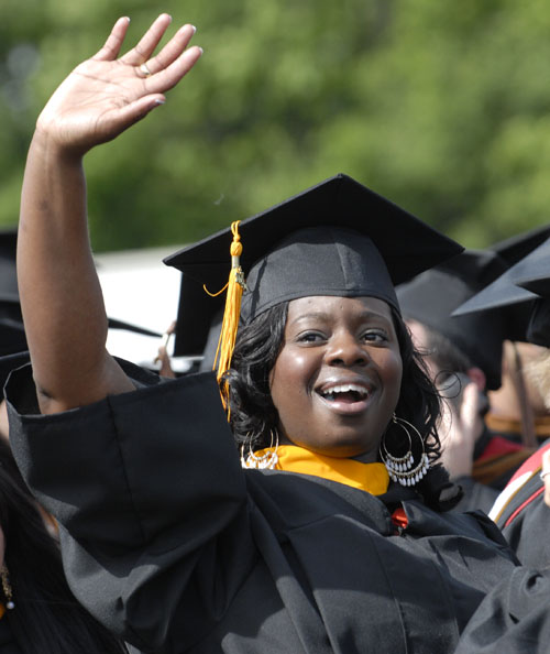 Woman student waving at crowd at graduation