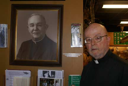 Fr. Ted posing with portrait of Hilary