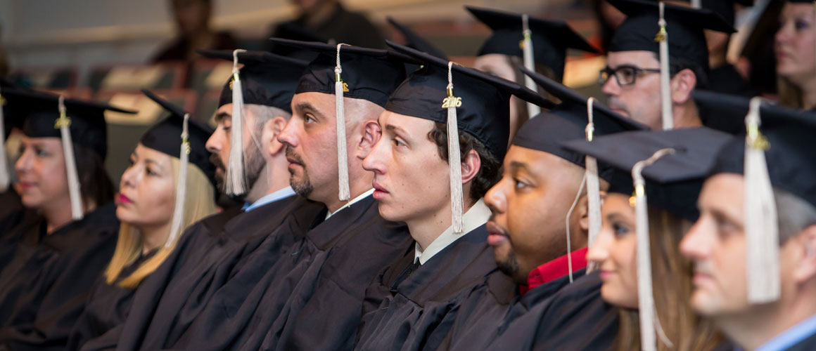 Benedictine University students sitting in cap and gown at Commencement