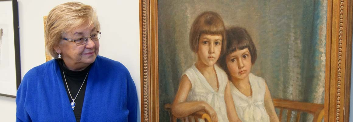 Susan Mikula stands next to a 1928 oil painting of her mother and aunt that hangs in her office at Benedictine University in Lisle, Illinois.
