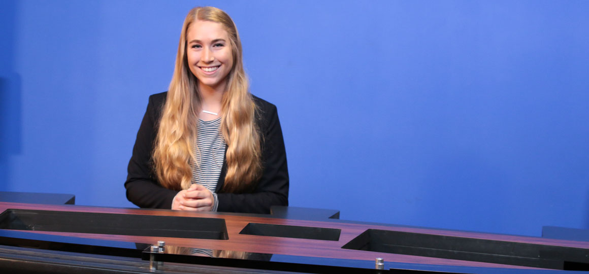 BenU junior Communications Arts major Molly Morley sits in front of a news desk donated to the University by NBC 5 Chicago.