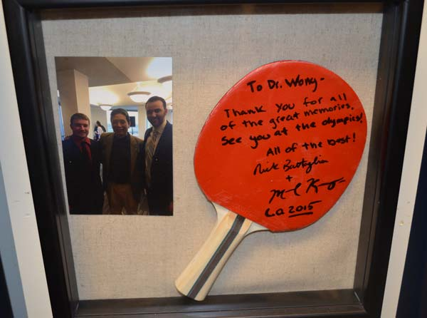 BenU Associate Professor Ovid Wong received a surprise gift from former students: an autographed pingpong paddle framed with a picture of Wong and two of his former students and pingpong partners.